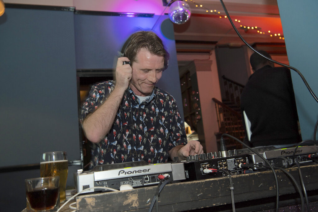 dj standing behind turntables and a mixer in the process of mixing some records