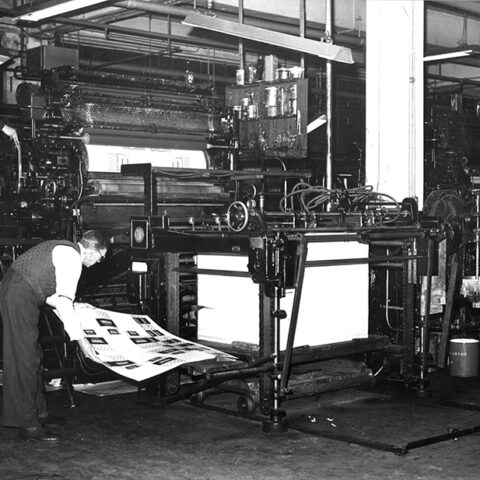 An old printing press with a man operating it