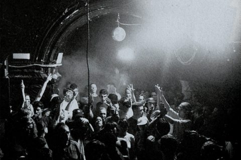 Black and white image of people dancing in a club