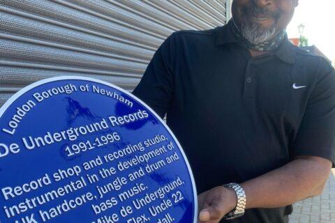 Uncle 22 holding the blue plaque outside 18 Sebert Road